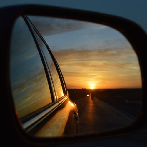sunset through the side mirror of a car